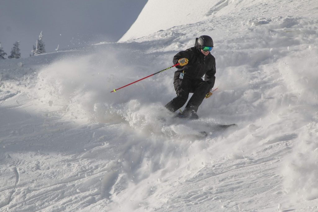 Man skiing and smiling on a steep powder-filled trail