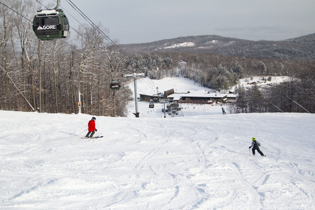 A wide open ski trail, a gondola, and a base area very snowy