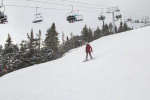 A New Quad lift and a lady snowboarder on a ski trail