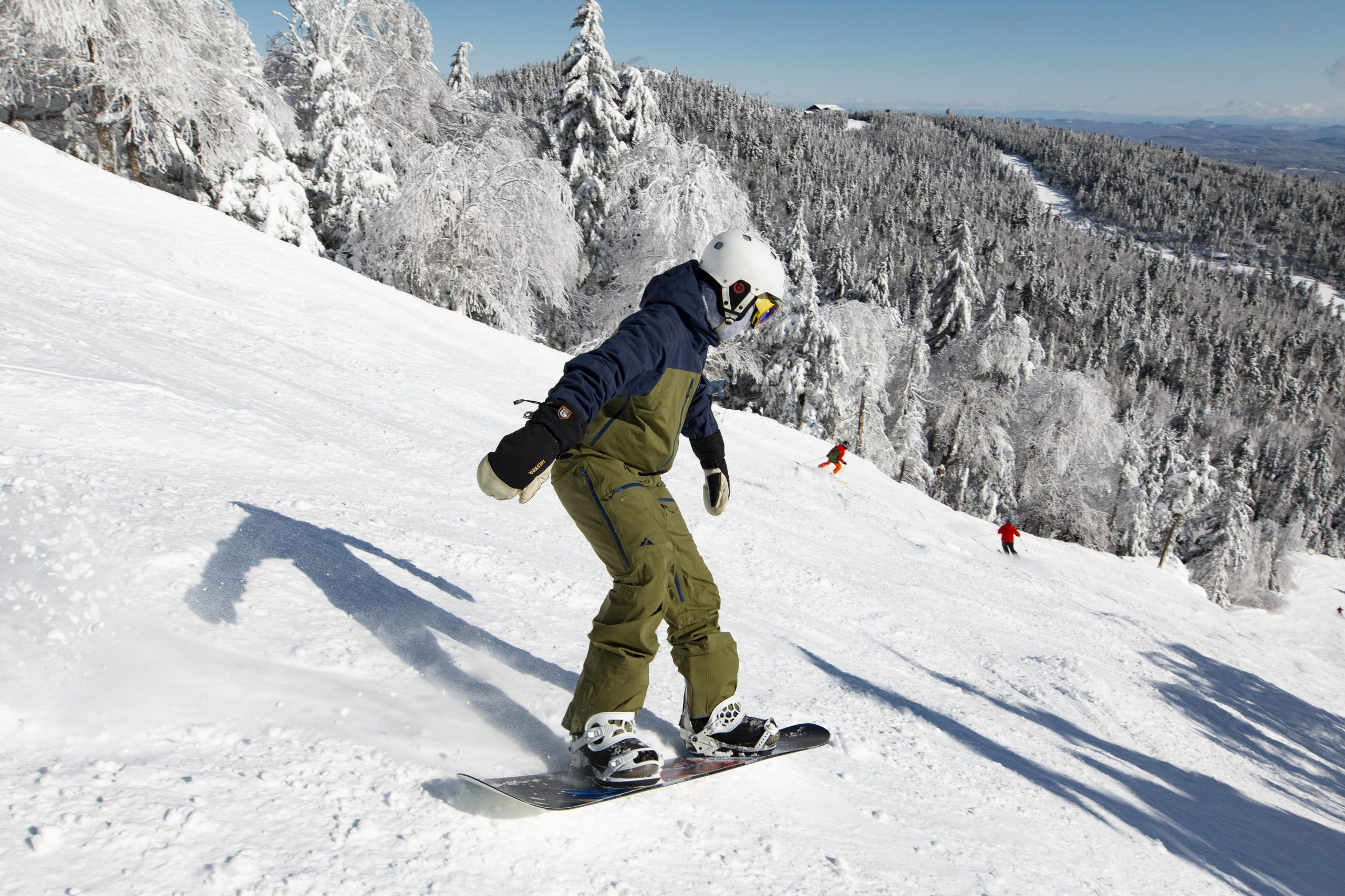 Snowboarder on a steep trail with a scenic view