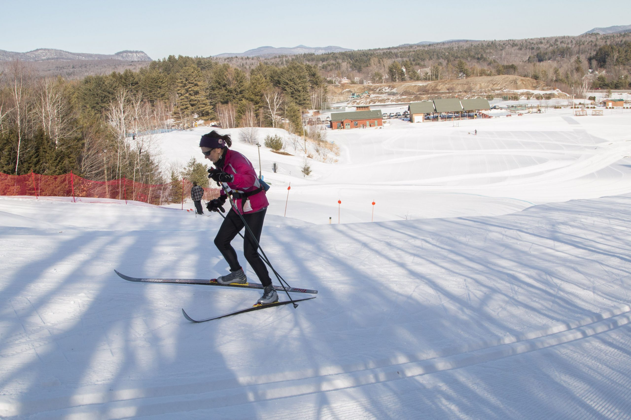 A lady climbing up a steep trail in Nordic Skis