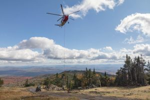 A Helicopter on top of a scenic mountain peak delivering concrete