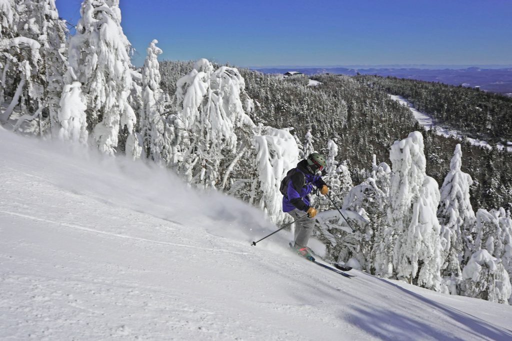 a skier on a steep trail with a mountain in the background