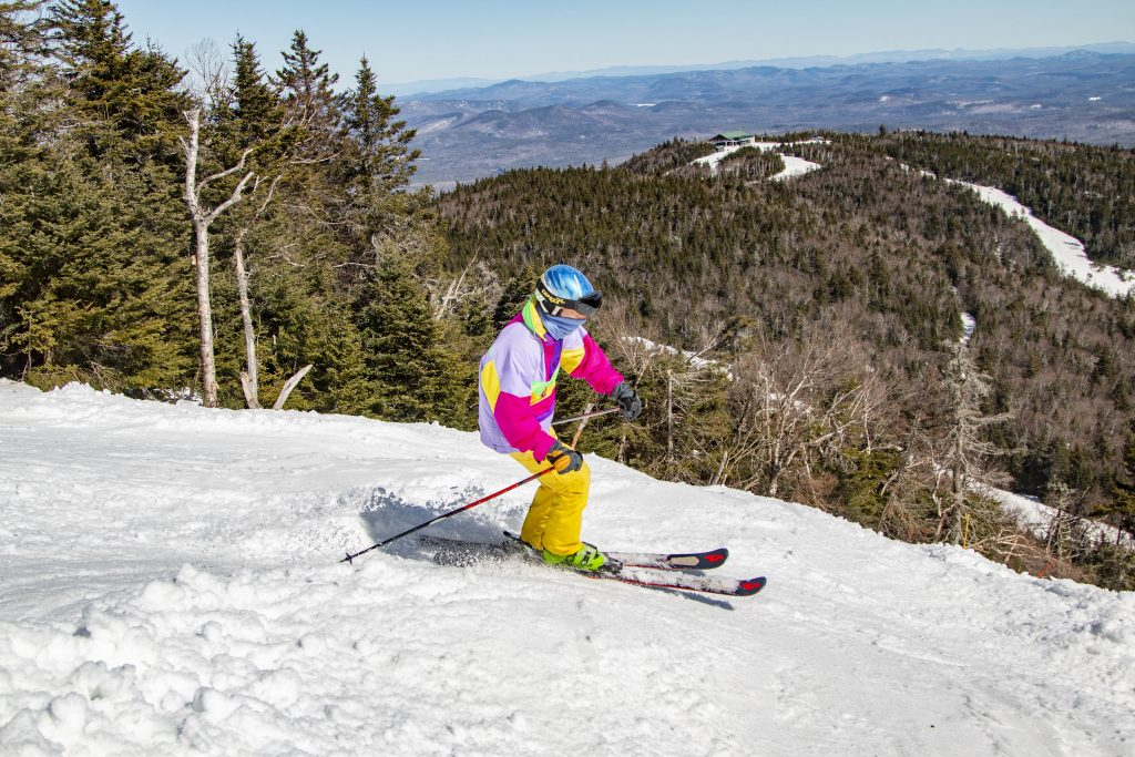 a man in bright colors on top of a ski trail