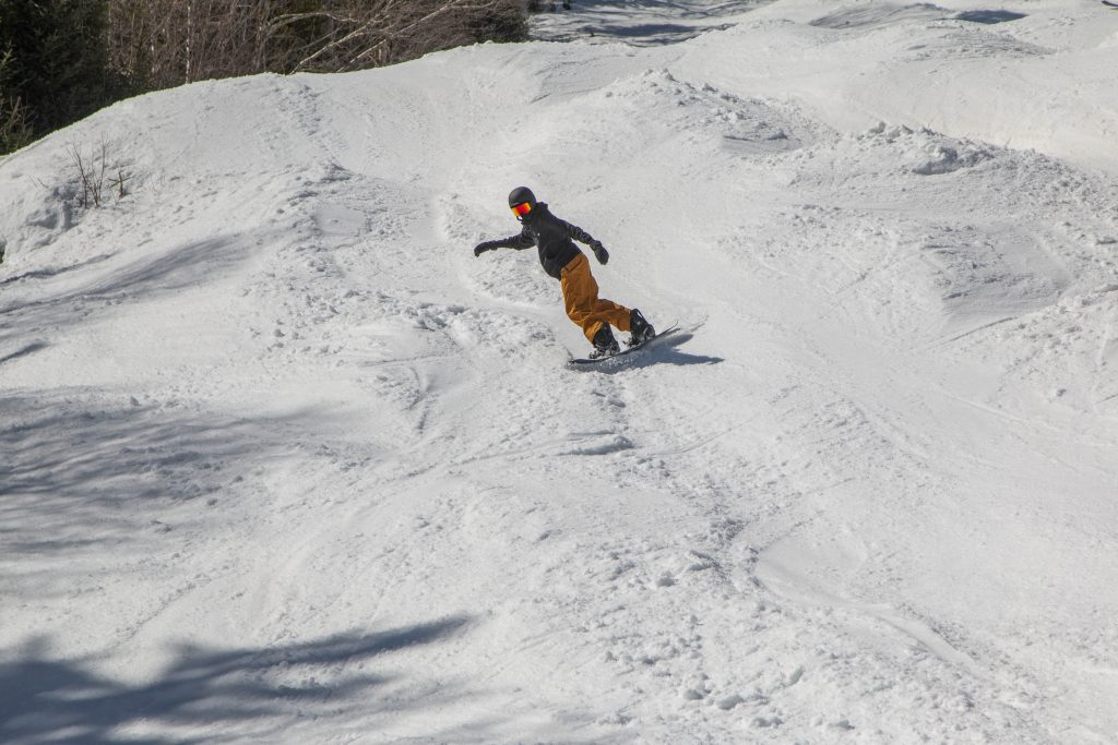 A snowboarder on moguls