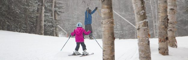 A dad and daughter skiing
