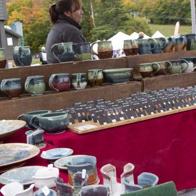 vendor display with earrings, bowls, mugs, and more pottery