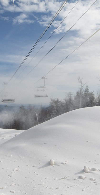 Snowmaking at the top of a ski trail, mounds of snow