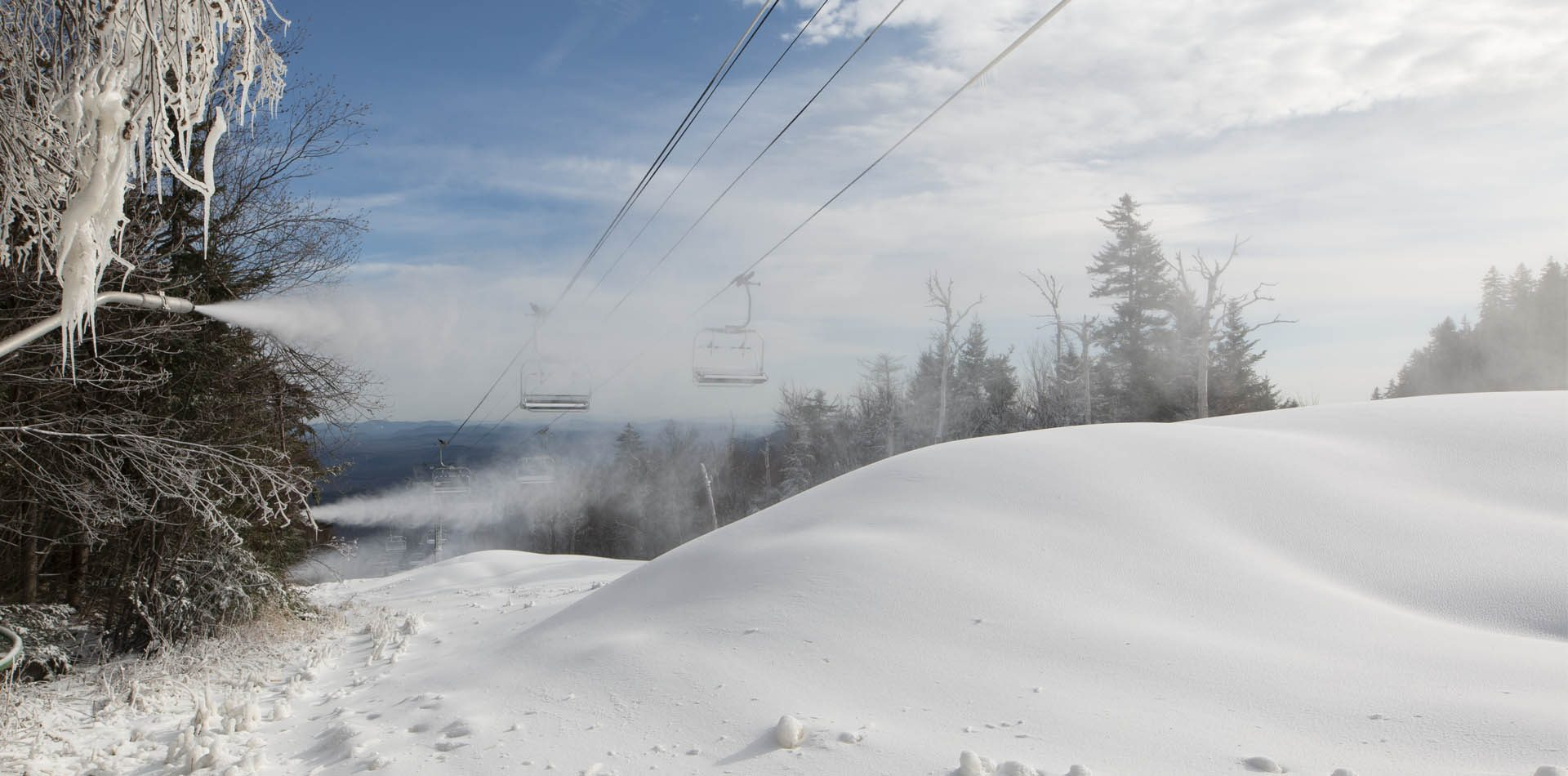 Snowmaking on the top of a ski trail on a blue sky day