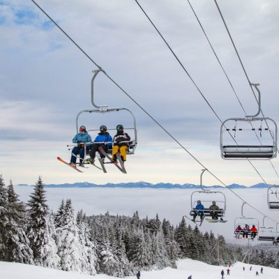 skiers riding high peaks quad at top of mountain